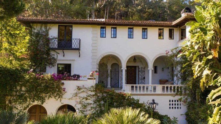 This is a view of the front of the house that showcases arches and pillars to its beige exterior walls complemented by the lush landscaping of thick shrubs and tall trees. Image courtesy of Toptenrealestatedeals.com.