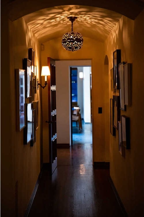 This is a beige hallway with hardwood flooring and multiple wall-mounted framed artworks on the walls. Image courtesy of Toptenrealestatedeals.com.