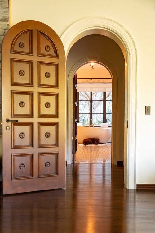 This hallway leads to a tall arched entryway with a matching detailed arched door. Image courtesy of Toptenrealestatedeals.com.