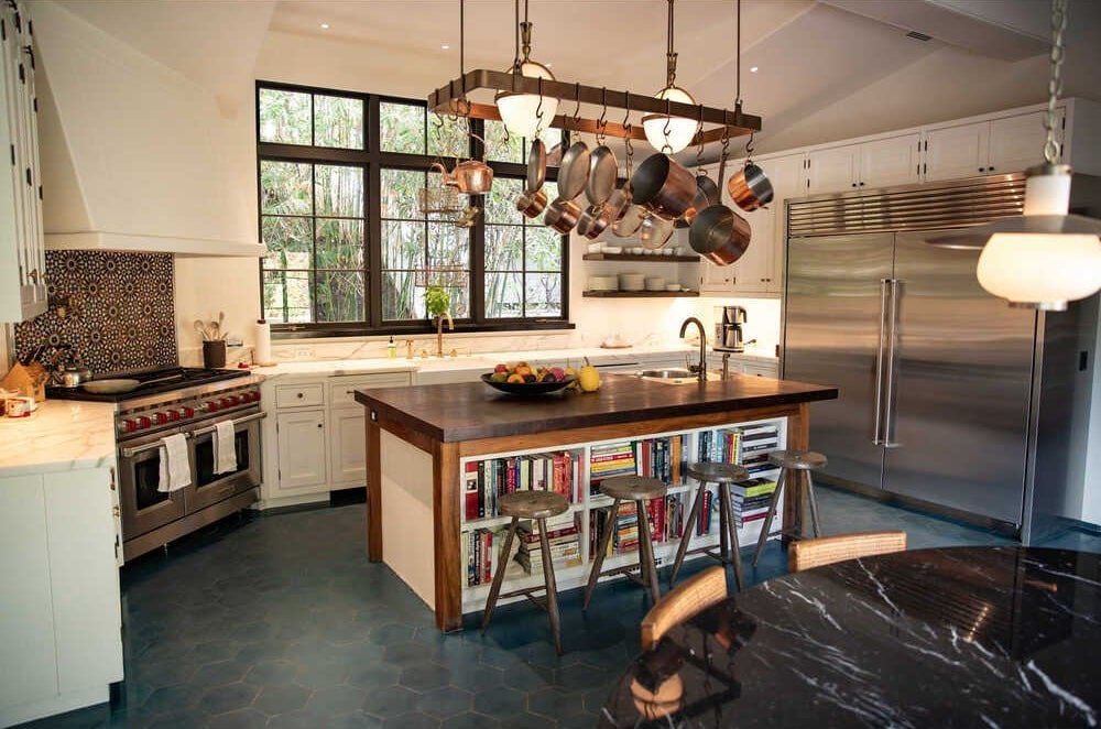 The kitchen has a large kitchen island topped with a large pot rack hanging from the beige ceiling that matches the walls. Image courtesy of Toptenrealestatedeals.com.