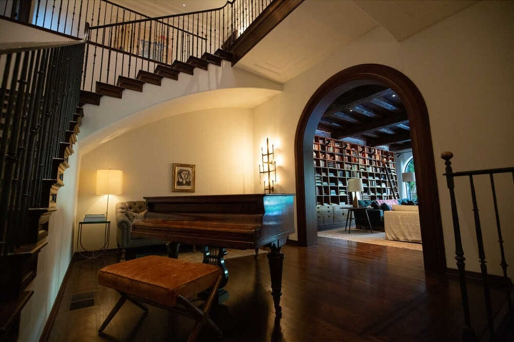 This is a close look at the grand piano near the large arched entryway of the library on the far side. Image courtesy of Toptenrealestatedeals.com.