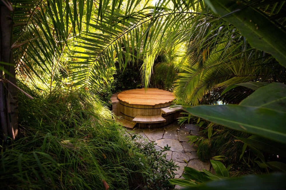This corner of the landscape has a hidden hot tub nestled amongst the thick shrubbery and tall tropical trees. Image courtesy of Toptenrealestatedeals.com.