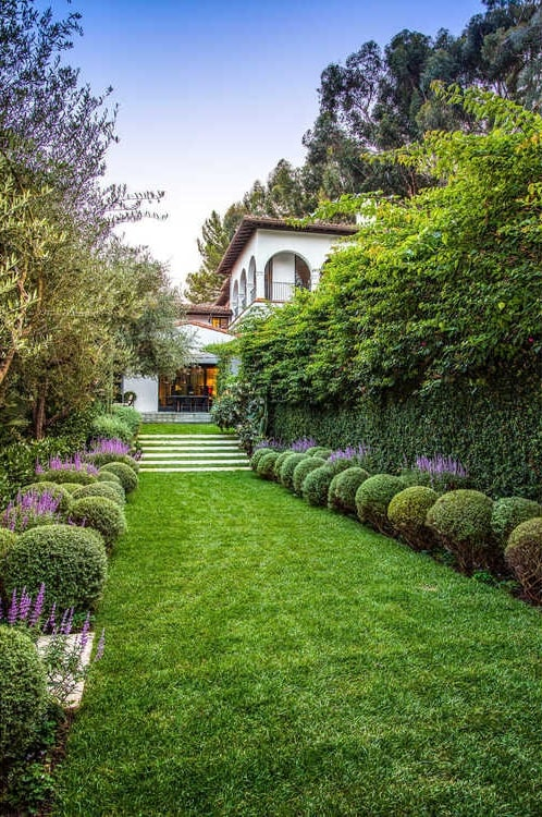 This is a close view of the portion of the garden that has colorful flowering shrubs and tall shrub hedges with a view of the house entrance on the far side. Image courtesy of Toptenrealestatedeals.com.