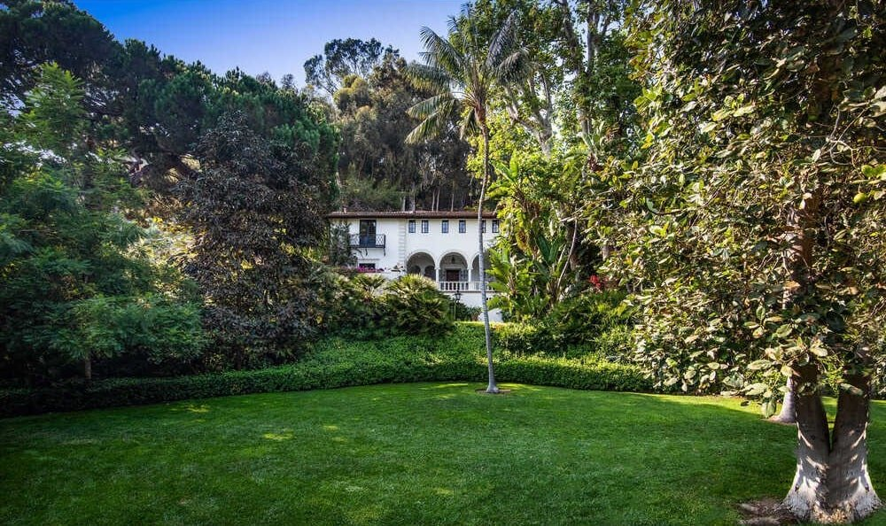 This is a far off view of the main house showcasing the large property filled landscaping of lush grass lawns, thick shrubs and tall trees. Image courtesy of Toptenrealestatedeals.com.