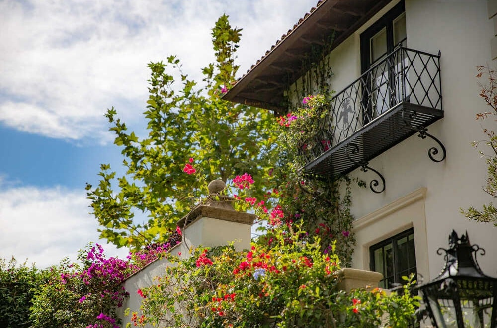 This is a close look at the balcony and beige exterior walls of the house adorned with creeping and flowering plants that bring colors to the neutral tones. Image courtesy of Toptenrealestatedeals.com.