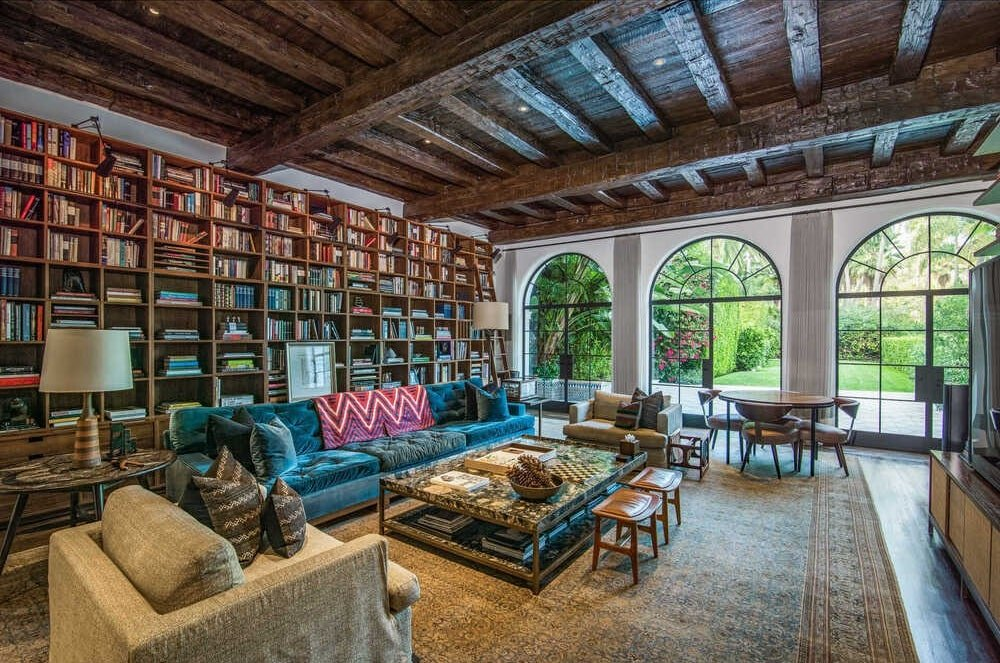 This is the library that has a tall wooden beamed ceiling that matches the built-in bookshelves behind the sofa set. Image courtesy of Toptenrealestatedeals.com.