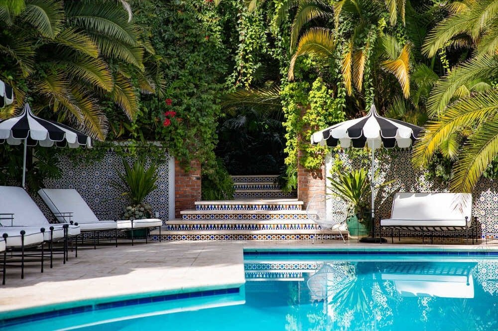 This is a close view of the swimming pool area with an entryway that is adorned with blankets of creeping vines and tall tropical trees. Image courtesy of Toptenrealestatedeals.com.