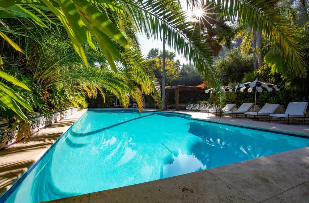 This is another view of the swimming pool area that has concrete walkways fitted with lounge chairs and lined with tropical trees. Image courtesy of Toptenrealestatedeals.com.