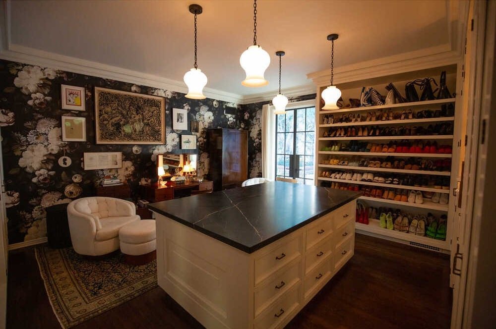 This is the walk-in closet that has a large island in the middle with white drawers and black counter that is topped with pendant lights. On the side are the shoe storage and a comfortable sitting area. Image courtesy of Toptenrealestatedeals.com.