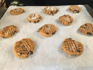 The cookie dough are separated and flattened on the sheet.