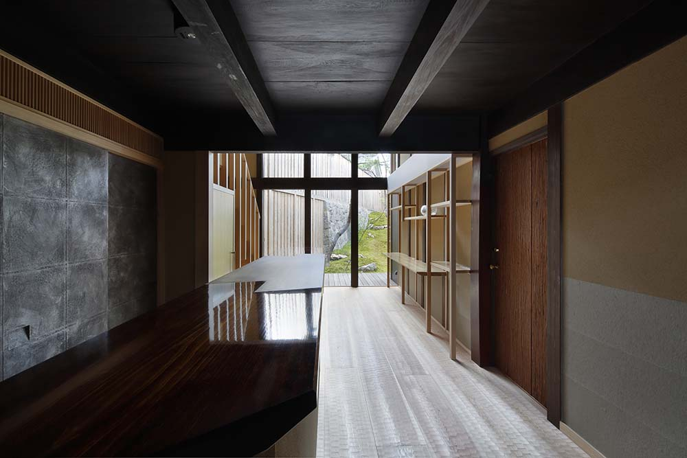 This is a close look at the lobby and reception desk of the hotel with a polished dark wooden countertop.
