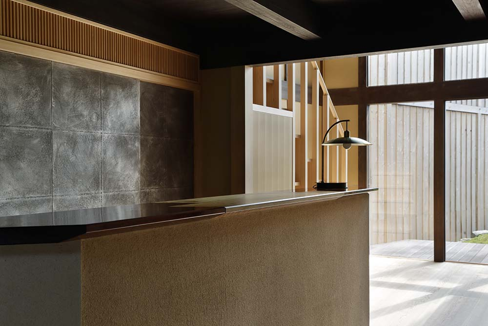 This is another look at the lobby and reception desk of the hotel topped with a wooden counter and a table lamp.