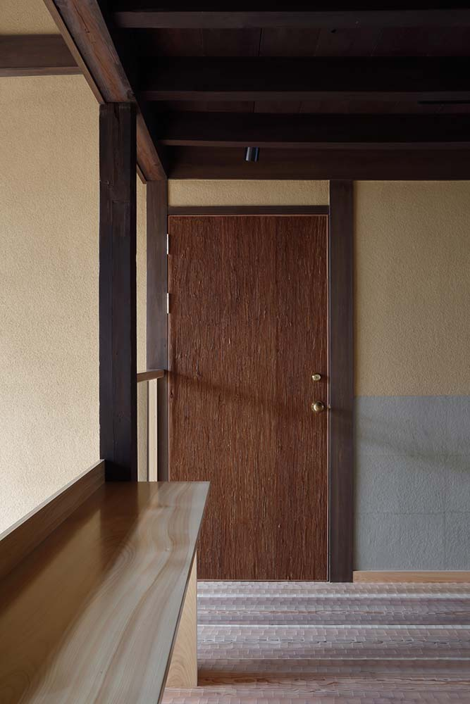 On the side of the indoor balcony is a wooden door that leads to one of the rooms of the hotel.