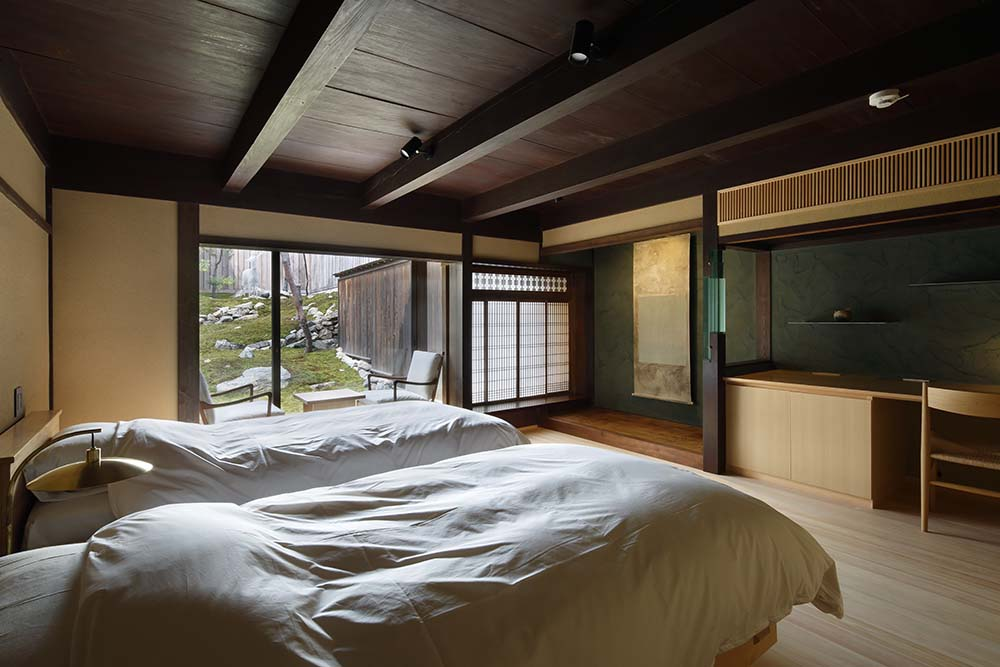 This is a close look at one of the bedrooms that has a couple of white beds complemented by the light hardwood flooring and dark wooden ceiling.