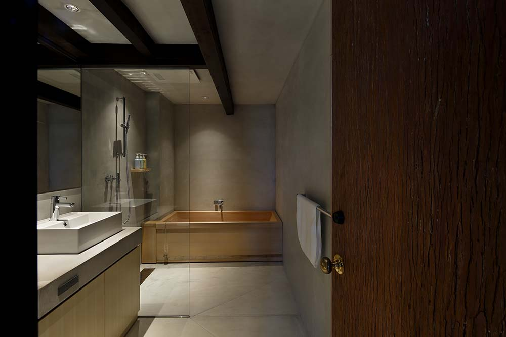This is a look at the bathroom that has a bathtub on the far side next to the shower area. These are complemented by the dark exposed beams of the ceiling.