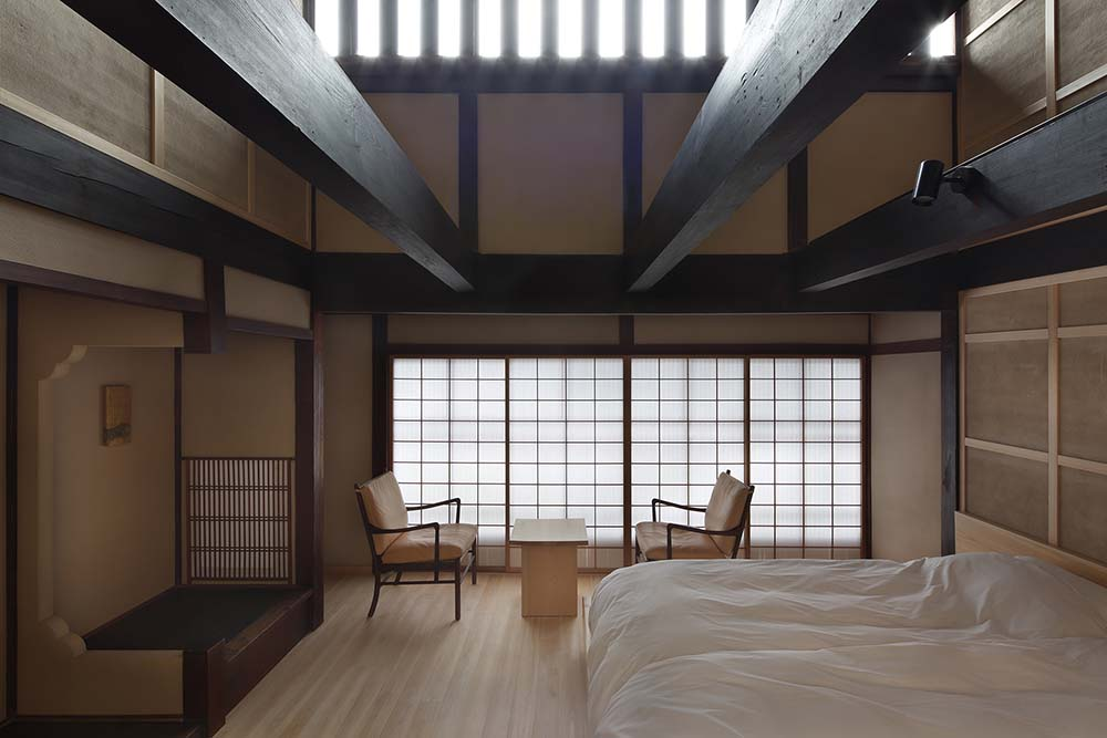 This is a close look at the other bedroom that has one large bed topped iwth exposed beams and has a lounge area by the windows.