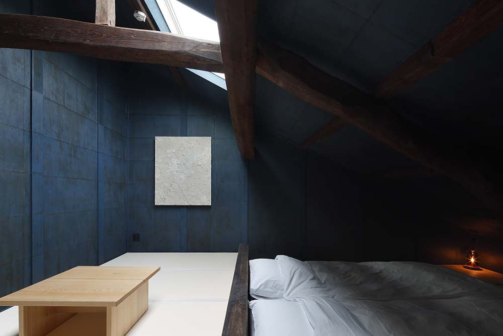 This is a look at another bedroom that has a low beamed shed ceiling above the couple of beds.