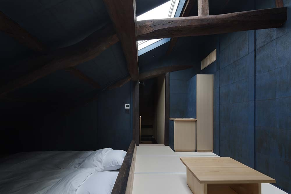 At the foot of the beds is a lounge area with a low wooden coffee table and a skylight above.