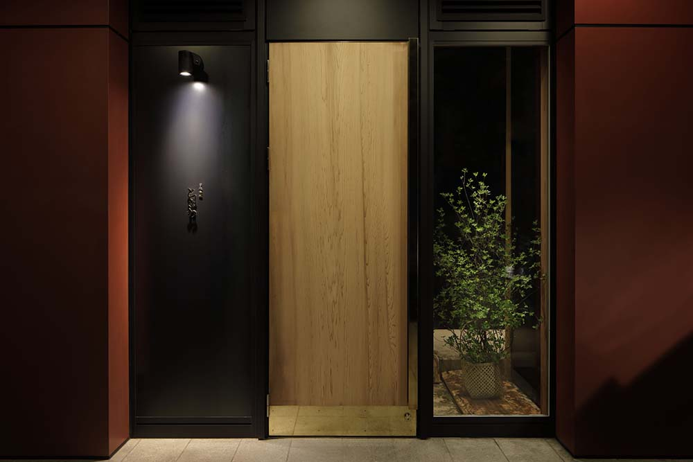 This is a close look at the front door of the Japanese Restaurant with a wooden door accented with a black wall and black frame.