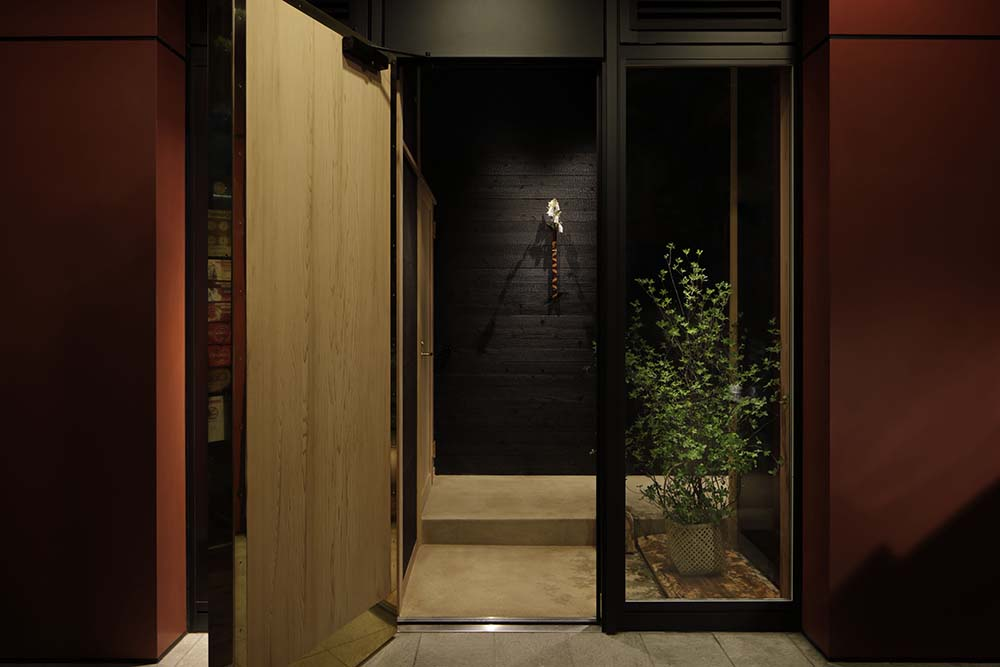 The side of the wooden main door has a glass panel adorned with a small potted plant.