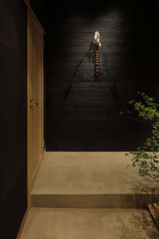On the far side of the foyer is a black wooden shiplap wall adorned with a wall-mounted flower display.