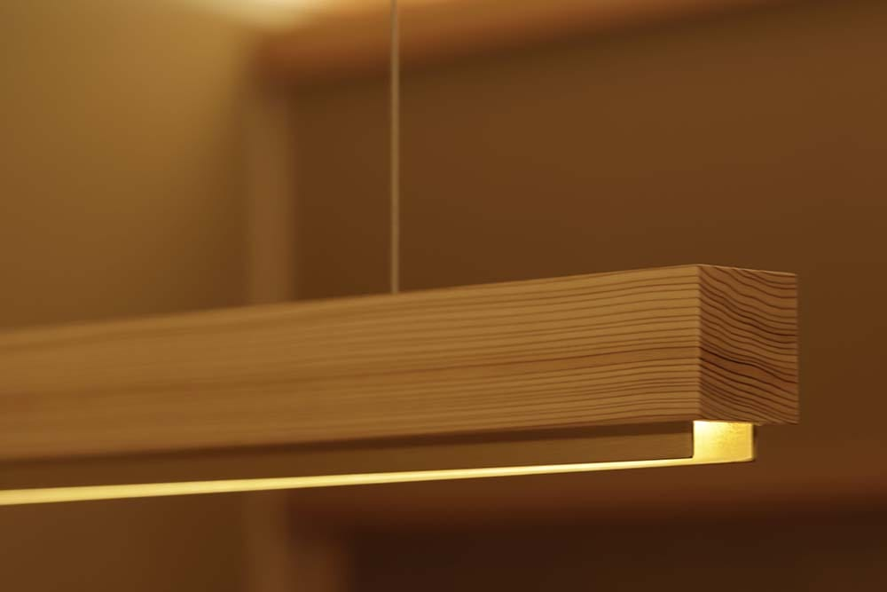 This is a close look at the wooden light fixture with a warm yellow light hanging over the table.