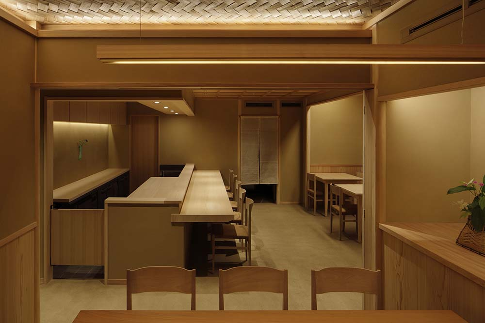This is a full view of the restaurant bar area with a set of chairs facing the built-in wooden table attched to the cooking area and preparation area.