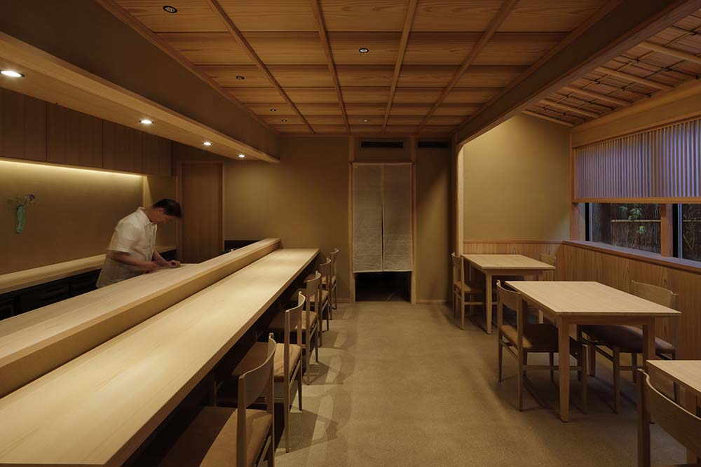 The wooden ceiling over this area is adorned with exposed beams and modern lighting over the food preparation area.