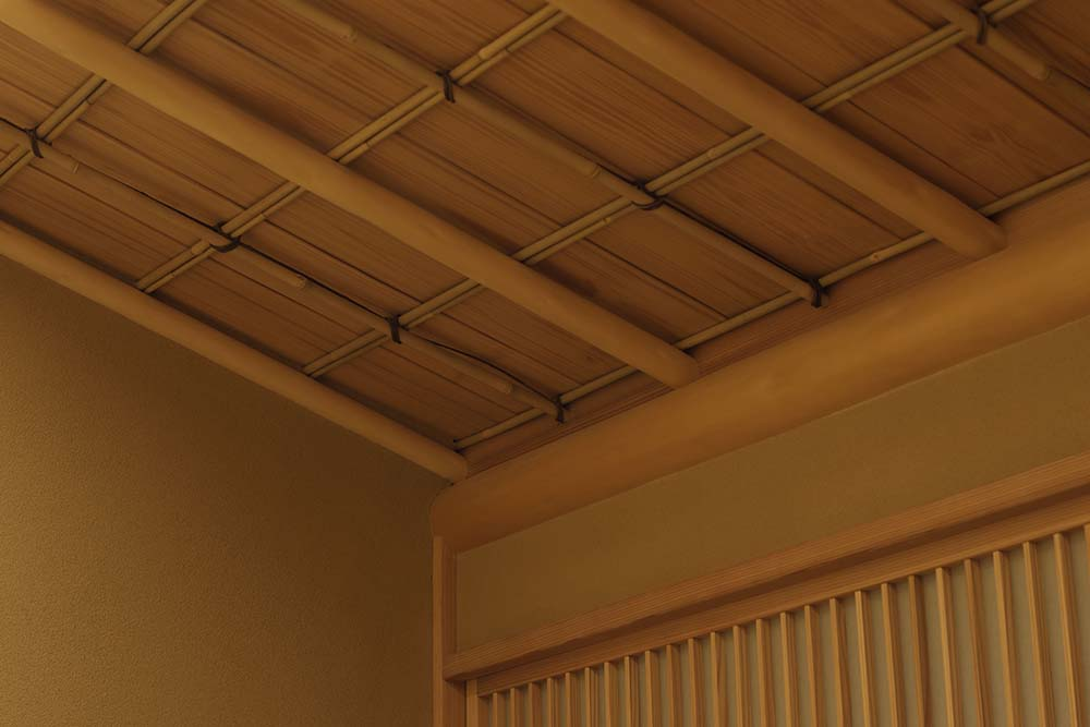 This is a close look at the wooden ceiling that has beams to match the walls.
