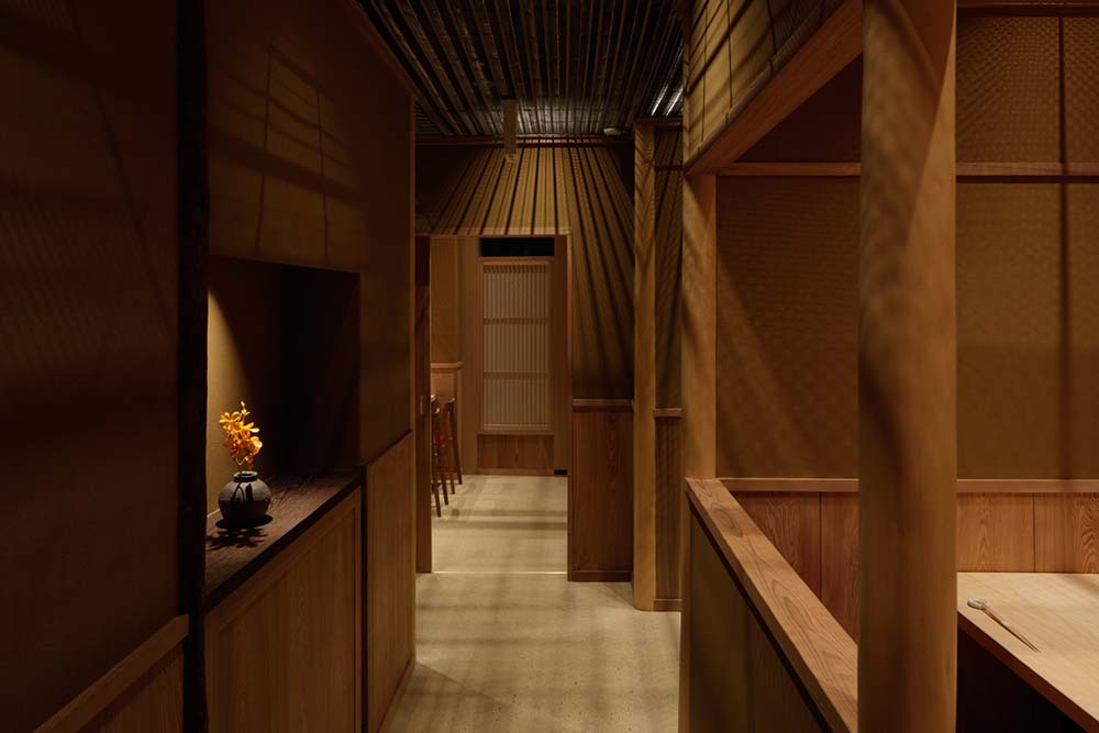This is a hallway within the restaurant that has a wooden alcove on the side with a decoration.