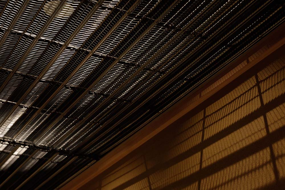 This is a close look at the ceiling that has metal screens that let light through..