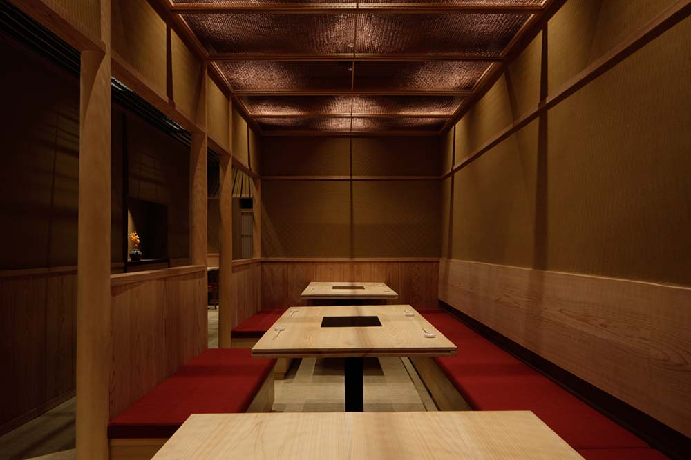 The tables of the dining are are contrasted by the bright red cushions of the built-in benches lining the walls.