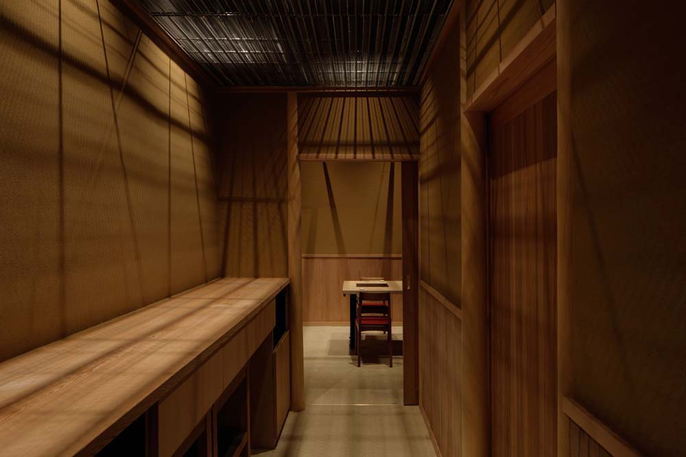 This is a hallway leading to the dining area with a alrge counter made of wood for food preparation.