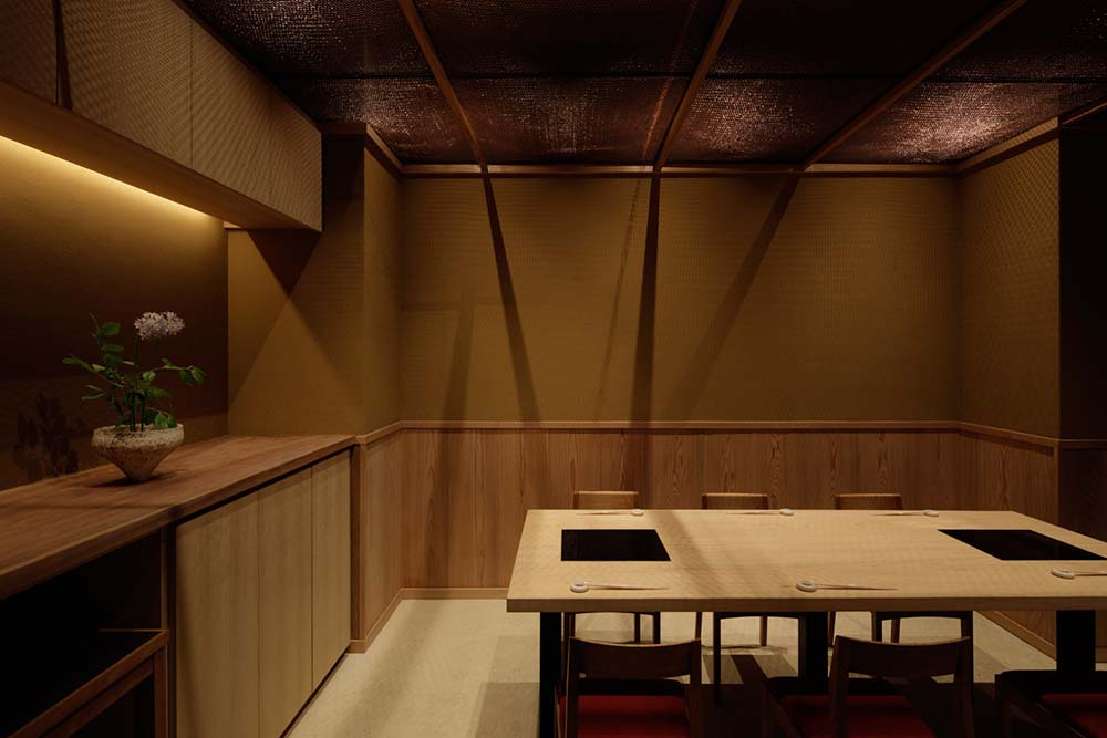 This is a close look at the side of the long rectangular dining table that has a window and counter for food preparation.