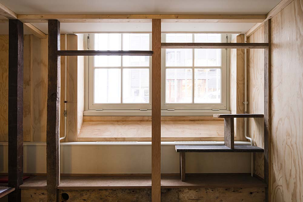 This is a close look at the other window with a built-in wooden bench and wooden shelves on the side.