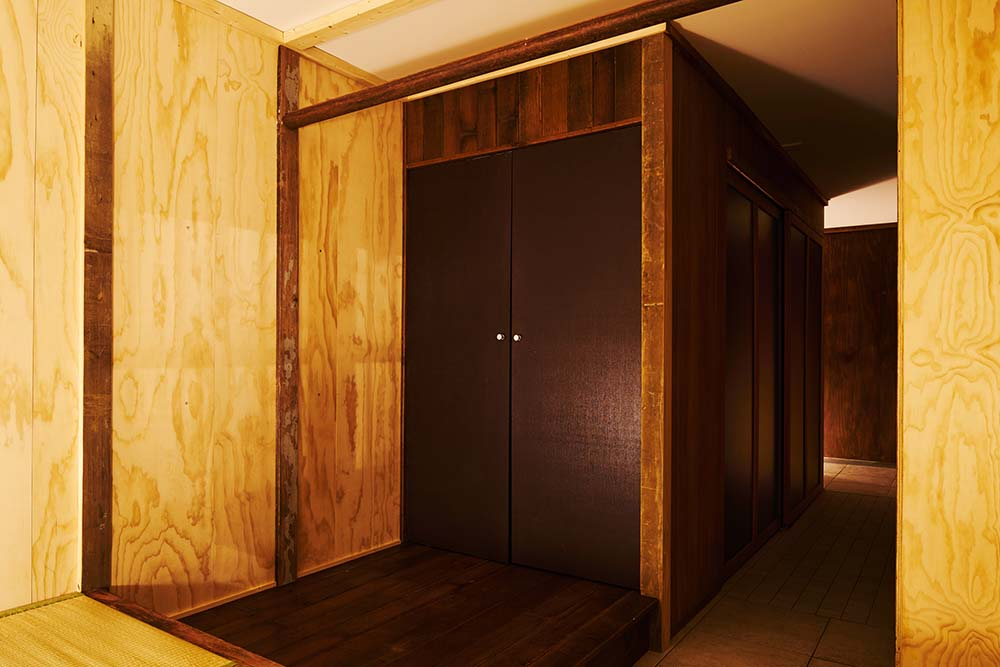 This is a close look at the dark wooden double door of the house with a matching dark wooden deck flooring.