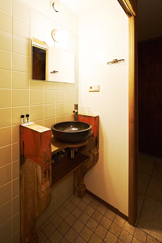 The bathroom has a rustic wooden vanity structure that stands out against the beige subway tiles.