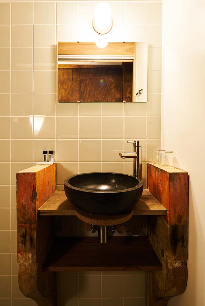 The wooden vanity has a dark bowl sink paired with a stainless steel faucet and a wall mounted mirror.