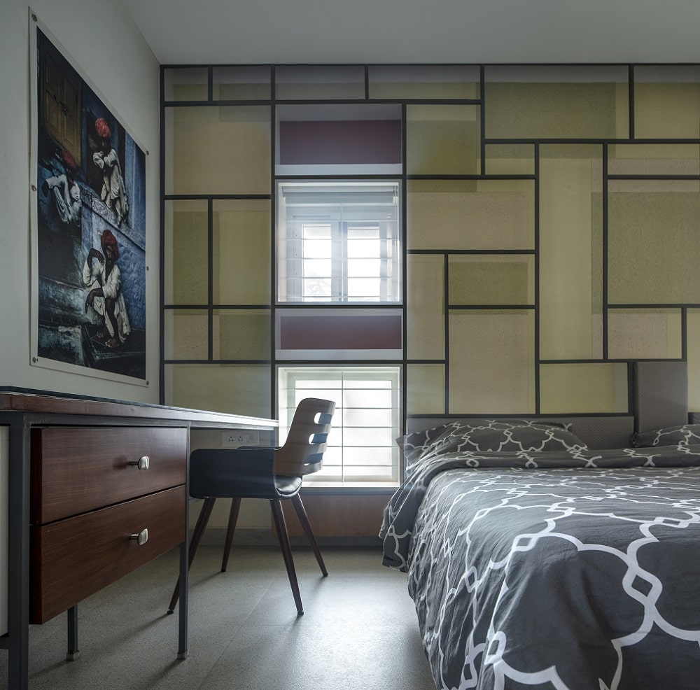 This is a close look at the bedroom that has a patterned sheet on its bed complemented by the geometric patterns of the wall behind the headboard.