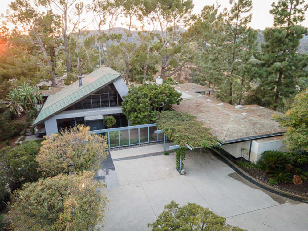 This is an aerial view of the house showcasing the tall angled and arched roof and the surrounding lush landscaping of tall trees and shrubs. Image courtesy of Toptenrealestatedeals.com.
