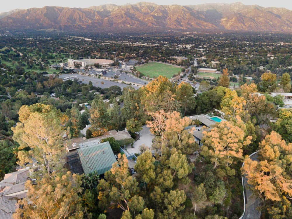 This is an aerial view of the whole estate showcasing the two houses and the tall trees that complement them. Image courtesy of Toptenrealestatedeals.com.