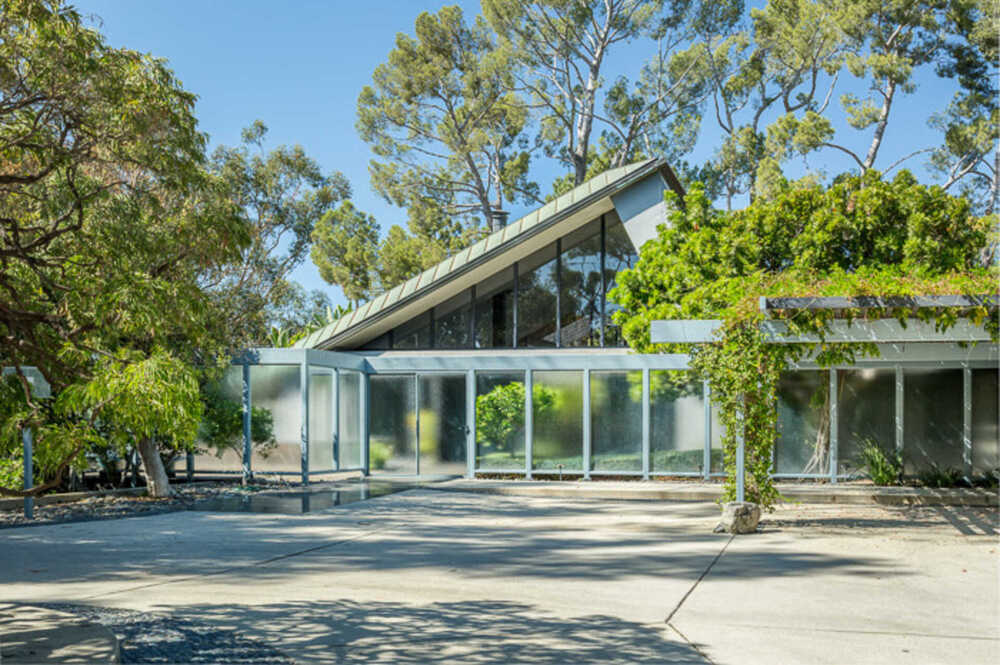 This is a front view of one of the midcentury houses with a tall roof, frosted glass enclosure and lush landscaping. Image courtesy of Toptenrealestatedeals.com.