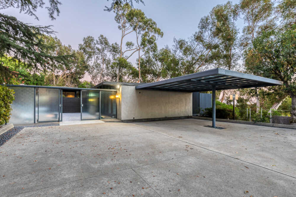 This is a view of the front of the other house that has a car port and glass main doors on the side of the concrete wall. Image courtesy of Toptenrealestatedeals.com.