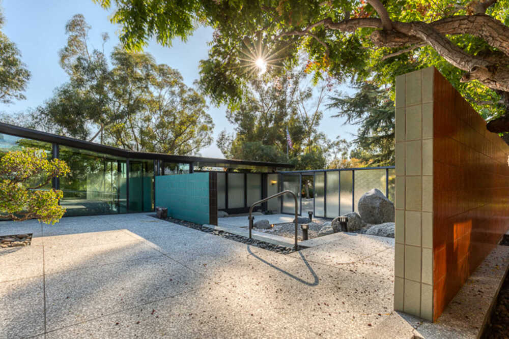This is another view of the front of the house showcasing more of the concrete walkways and glass walls supported by metal beams. Image courtesy of Toptenrealestatedeals.com.
