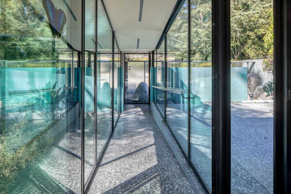 This is a hallway within the house that has glass walls on either side and a concrete walkway. Image courtesy of Toptenrealestatedeals.com.