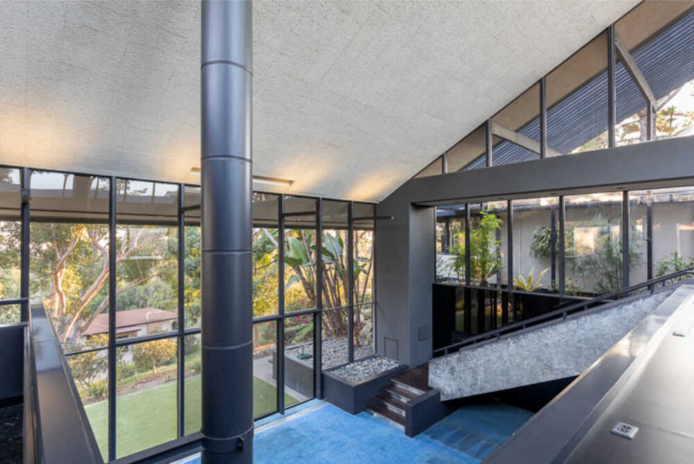 This is another view of the expansive living room area from the vantage of the indoor balcony showcasing the large chimney duct that goes straight up to the roof. Image courtesy of Toptenrealestatedeals.com.