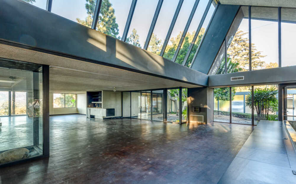 Across from the indoor balcony of the living room is the kitchen and dining area areas on the far side brightened by the bright glass walls. Image courtesy of Toptenrealestatedeals.com.