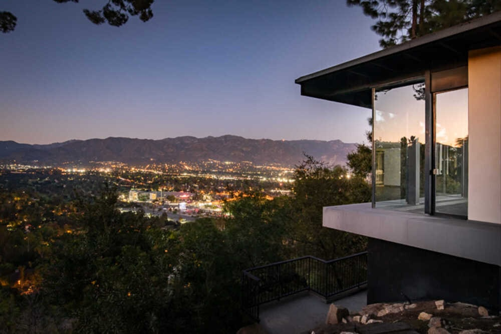 This is a nighttime look at the view of the house that is maximized by the glass walls facing the bright lights of the city in the distance. Image courtesy of Toptenrealestatedeals.com.
