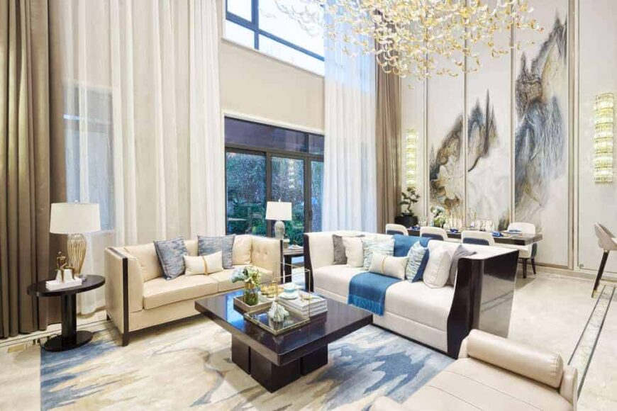 This is a look at a hollywood glam-style living room with modern elements, bright sofas and dark coffee table under a large decorative lighting.