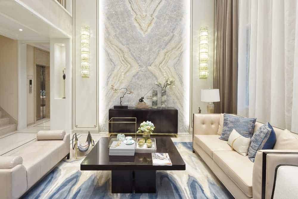 This is a close look at a hollywood glam style living room with bright beige elements contrasted by the dark coffee table in the middle of the two beige sofas.